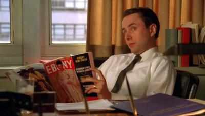 a screenshot of Pete Campbell from Mad Men reading an issue of Ebony and raising his eyebrow like 'What?'